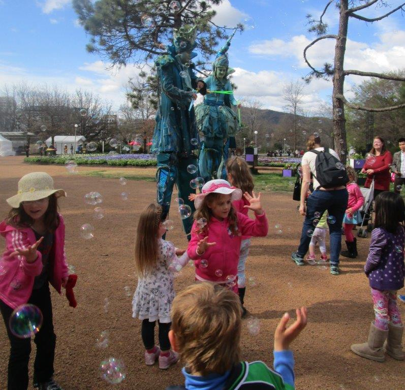 Floriade stilt-walkers blowing bubbles for the children