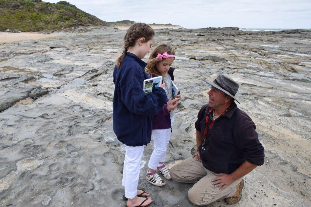 Tom the Palaeontologists patiently teaches the girls about a different age at the Dinosaur Dig