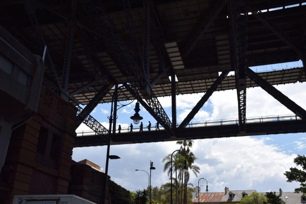 Climbers walking the Harbour Bridge catwalks high above the Sydney Rocks area