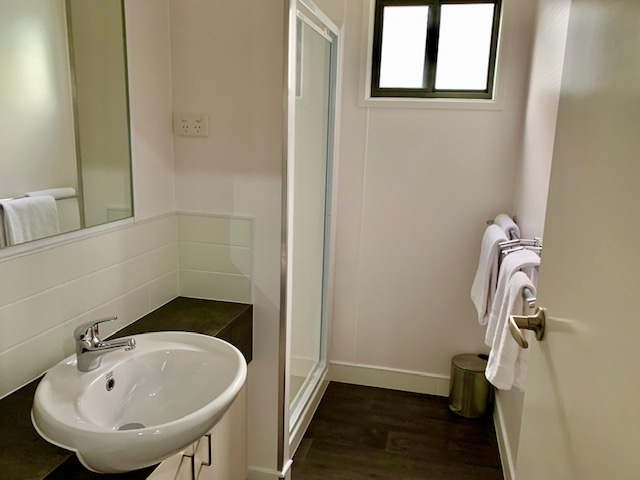 The bathroom has a shower and vanity, with the separate toilet located on the opposite side of the hallway